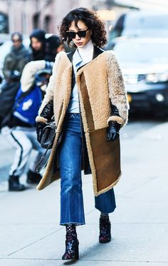 A fur-paneled coat is worn over a white turtleneck, cropped jeans and statement booties