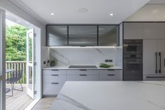 The kitchen is a streamlined galley design with a longer island containing the sink. The overhead cupboard section has fluted, smokey glass inserts with blackened steel frames.  The fluted design element has been repeated on the back of the island panels. The soft lines and colour of the benchtop and splashback contrasts the strong vertical design elements of the framed steel and the vertical fluted glass and island panels.A pantry is hidden behind pocket doors and contains a benchtop… Kitchen Space, Interior, Interior Design Solutions, Vertical Design, Building A House, Industrial Kitchen Design, Renovations, Kitchen Renovation, Kitchen Design