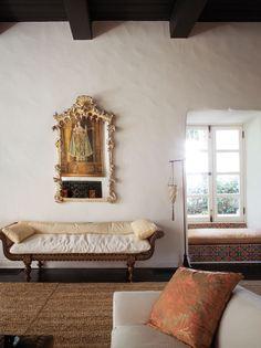A German Rococo mirror hangs above a 19th-century Indian bench.
