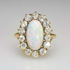 Romantic 1900's 3.31ct t.w. Opal & Old European Cut Diamond Halo Ring 14k | Antique & Estate Jewelry | Jewelry Finds Price: $3600.00  A stunning natural vibrant opal and old European cut diamond ring measuring 20.41mm x 15.23mm overall, on a half-round shank which measures from 1.70mm-2.60mm in width and 1.24mm-3.30mm in depth. A fantastic size and presentation and will trump any other antique opal and diamond ring out there!