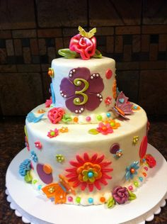 8 inch base with a 4 inch top. Oh how I want a 5 or 7 inch cake pan:)   Frosted in buttercream. Modeling chocolate flowers and accents.  Lots of plunger flowers and butterflies.