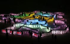 People visit a maze which was built with ice bricks and illuminated by coloured lights ahead of the 31st Harbin International Ice and Snow Festival.