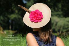 Tocado disco realizado con base de parasisal en color almendra adornada con una peonía en color rosa fucsia y una pluma de faisán. Elegante y sofisticado, es perfecto para una boda de mañana.