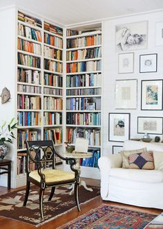 Absolutely gorgeous reading corner, white walls and book shelves, wooden flooring, traditional rugs.