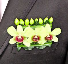 """Pocket Square"" boutonniere with dendrobium orchids and hypericum buds"
