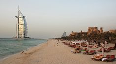 A few people relax on Dubai Beach with the Sheth Tower standing 32-stories tall in the background.
