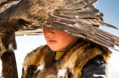 A young Kazakh boy with his eagle which will perform at the traditional Eagle Festival held in Bayan-Ölgii, Mongolia