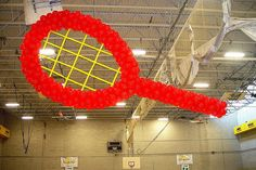 Tennis Record Balloon Sculpture 20' long, 10' wide balloon sculpture of tennis racket for a competition.  The production was relatively simple compare to the hanging process.  But we have managed!  For some reason, the tennis racket strings, made out of long balloons (usually used to twist the balloon animals) surprised more people than the balloon sculpture itself!    Albany NY     Corporate Events