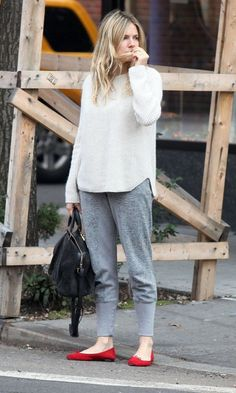 Pair a white oversized sweater with grey sweatpants for a lazy Sunday brunch. Choose a pair of red suede flats to va-va-voom your outfit. Shop this look on Lookastic: https://lookastic.com/women/looks/white-oversized-sweater-grey-sweatpants-red-ballerina-shoes-black-tote-bag/8525 — White Oversized Sweater — Grey Sweatpants — Black Suede Tote Bag — Red Suede Ballerina Shoes