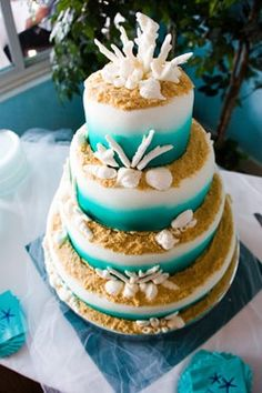 i love the fading blue tiers and coral! i dont want the cliche beachy/tropical wedding though. so maybe loose the realistic sand seashells for a more minimalist look!