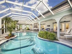 Pool with planters and screened lanai with plenty of covered space in Pelican Bay Woods in Naples, FL