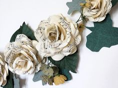 A big floral Garland with Paper Roses and Ivy. With its old music sheets, this rose swag would look perfect as wedding decoration on a Shabby Chic,