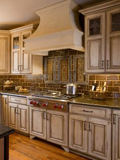 Inset tile work -slate and dark brown, contrasts with pale glazed cabinets.
