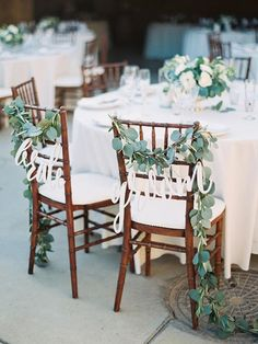Bride and groom signs written in script and greenery decorate wedding chairs at an outdoor wedding ~ http://www.stylemepretty.com/2015/09/21/intimate-summer-sunstone-villa-wedding/