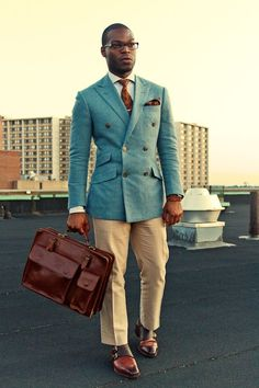 Shop this look for $517:  http://lookastic.com/men/looks/chinos-and-double-breasted-blazer-and-pocket-square-and-dress-shirt-and-tie-and-briefcase-and-double-monks/1432  — Khaki Chinos  — Light Blue Double Breasted Blazer  — Brown Paisley Pocket Square  — Grey Vertical Striped Dress Shirt  — Brown Paisley Tie  — Brown Leather Briefcase  — Brown Leather Double Monks