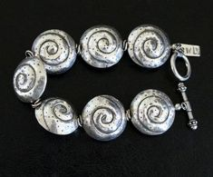 This attractive Bracelet is comprised of 7 Hill Tribe Silver Coiled Shell Beads that are in diameter. The Shell Beads are shaped like saucers, with subtly oxidized etched coils and dots providing Metal Beads, Silver Beads, Ring Spacer, Double Ring, Silver Rounds, Ring Bracelet, Bracelet Designs, Jewelery, Jewelry Design
