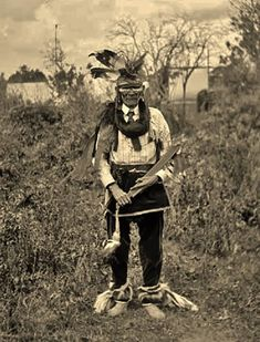 older ojibwa male wearing dress for war. [He wore proudly the double insignia of his success as a warrior - feathers in his headdress and skunk skins attached to his ankles. https://archive.org/stream/chippewamusic02densuoft#page/86/mode/2up page 86]