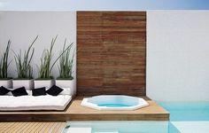 Piscina com entorno de grama e deck pequeno para apoiar poltronas