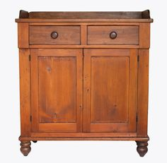 Lot 55: 19th C. Two-Door Cupboard - Poplar and pine, dovetailed gallery top, flanking dovetailed drawers with dark walnut pulls, inset panel doors through mortised and pegged, two-shelf interior, original key and lock, all on four turned double bun feet, 47″ h, 41″ w, 17″ d, (ex. Fertig collection).