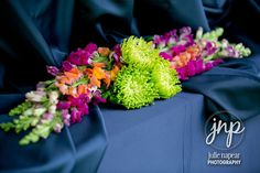 Trying to think of a way to add a pop of color to your event? This floral detail on the buffet is it! Flowers by Bluebells