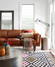 A mixture of colorful tribal prints against metallic accents and leathergive this room a lot of personality. Keep the windows simple with unassuming roman shades.