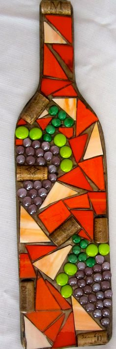 Unique mosaic glass wine bottle wall hanging made using a wooden base, colored glass, colored gems and wine corks.  Dimensions of the wine bottles are: 21.5 x 5.75 inches  Wine bottle wall hangings are available in various colors, including: Red Orange Yellow Green Blue (dark and light) Purple Pink Brown Black/White Rainbow Teal  Each comes with a pre-installed wall hanger, making it ready to hang straight out of the box.  Each is handmade and one-of-a-kind. Wine bottle surface may be uneven…