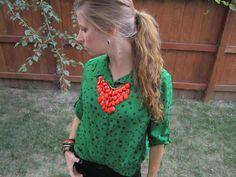 orange statement necklace, green polka dot shirt, black jeans, leopard flats