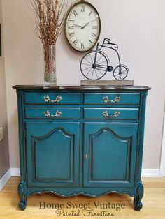 """I am in love with this color! It's a beautiful deep peacock called """"feathered nest"""" by Heirloom Traditions Paint. I distressed the edges and black glazed to keep that vintage look and kept the original hardware. The top could not be restained due to the many years of wear/imperfections so I did the next best thing and painted it to look like wood! :)"""