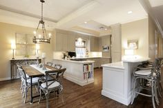 Note the beautiful Carrera marble counter tops, subway tile backsplash, under-cabinet lighting, bookshelves for cookbooks, & an appliance garage for your toaster or coffee maker. There is also a built-in microwave oven and designer window coverings.