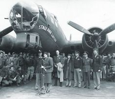 A host of celebrities that included Prime Minister Winston Churchill's daughter Mary Churchill (at the mic), actor Laurence Olivier (partially obscured by her), Alfred Lunt (to Olivier's left), and actress Vivien Leigh (to Lunt's left) joining in the April 1944 christening of a B-17 bomber named for the soon-to-be-opened London canteen.