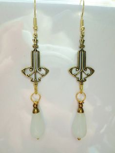 Long and elegant drop earrings with Art Deco design pendants and Czech glass opal drops. Complete with delicate bead caps. The total length