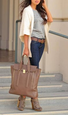 Waistlength dark hair, white sweater with elbowlength sleeves and thighlevel hem over grey tee, brown belt through blue denims, large brown satchel
