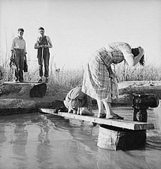 Oklahoma migratory workers washing in a desert hot spring in California - Dorothea Lange