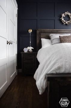Navy Master Bedroom- King Bed with white bedding, wooden headboard and moulding wall