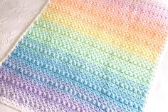 Crochet pattern for Rainbow Popcorn, a beautifully textured crochet baby blanket. Instant download PDF pattern - not a finished blanket. This sweet blanket is crocheted with two strands of yarn for a pretty mixing of the rainbow colours as you move through the blanket. The popcorn stitch adds texture and interest. The pattern includes full instructions, plus photos and instructions for the popcorn stitch.  Instant download so you can get stitching right away!  This blanket is relatively…