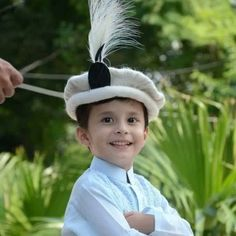Child wearing a traditional  wool Chitrali Topi (hat) with feather - Pakistan.