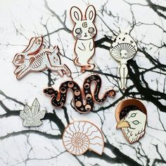 Bones and shadows . . [Image description: 7 enamel pins arranged on a photograph of tree branches. The pins are a rabbit skeleton by @lovesoup a rabbit ghost by @juicette a mushroom girl by @gildedcreaturesart a snake by @afera_handmade and @kwtallantdesigns a crystal by @tumbleandrose an ammonite by @milkandmoonuk and a raven by @beastsoftheunknown ] . . . . #enamelpins #lapelpins #pingame #pinstagram #enamelpin #lapelpin #hardenamelpin #pinart #collector #pin #pins #pinbadge #pincollector…