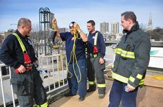 Winnipeg Fire Fighters collect donations in their boots for Rooftop Campout