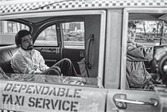 A film still from Taxi Driver features Robert De Niro in the driver's seat and the director Martin Scorsese in a cameo role as a jealous husband, by Steve Schapiro, 1976.
