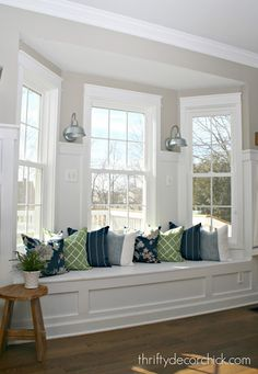 Kitchen window seat with sconces and colorful pillows