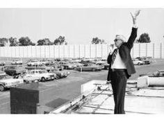 Robert Schuller before crystal cathedral giving Sun. Services from roof of snack shop of the Orange drive-in.   (Before swap meet crowd)