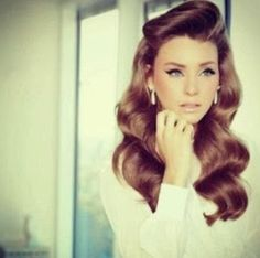 The big side-swoosh bangs and soft curls gives the 60s makeup (pale lip, thick black eyeliner) a more modern and loose look, vs the usual straight up stiff bouffant