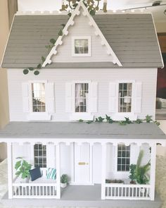 A beautiful New England Style house painted with soft grey walls, dark grey roof and patio and white shutters and wood accents. The interior has been designed and decorated to a high standard with battery operated fairy lights. All furniture has been made so that if items break as Im
