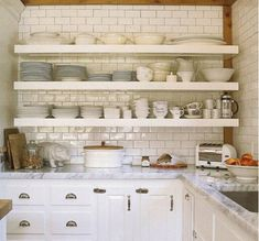 open kitchen shelves - dishware storage on white cantilevered shelves mounted on white subway tile - house beautiful via atticmag
