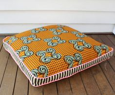 Dofu – yellow wax print floor cushion – designed by Maker & Merchant, Brisbane. Made from African wax printed cotton. The reverse of the cushion is the same as the front and has a zip closure. This walled cushion measures 70cm x 70cm and contains a feather insert. It includes Neon pink piping and features a black and cream striped edge. The cushion is easy to care for; cold hand wash. Dry in the shade (no tumble dry or dry clean) and iron inside out to protect the print. – All of our ...