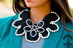 Collar babero en blanco y negro, realizado a mano con cuentas de bisutería y bolas de coral blanco.