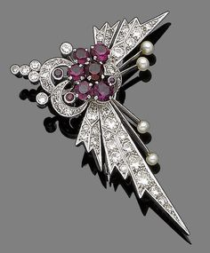 A ruby, seed pearl and diamond brooch  Of abstract design, set throughout with single and brilliant-cut diamonds, radiating spokes terminating in seed pearls, centrally-set with circular-cut rubies, diamonds approx. 1.45cts total, length 5.0cm. Vintage or Vintage style, possibly Retro.