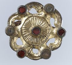 Whorl-Shaped Brooch; 550-650 CE; Frankish Garnets, worked in the cloisonné technique, featured prominently in the luxury jewelry of the Franks. Jewelers would solder small compartments arranged in geometric patterns onto the surface of a metal disk. In those cells, or cloisons, they would place a textured piece of gold foil, which would show through the thin translucent garnet that would then be set on top.