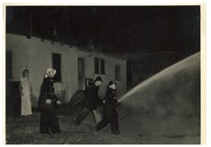 Firefighters using hose with girl