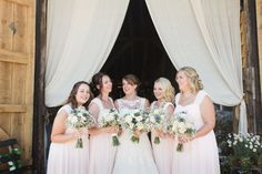 bride and bridesmaids in soft pale pink at titchfield barn smiling and laughing